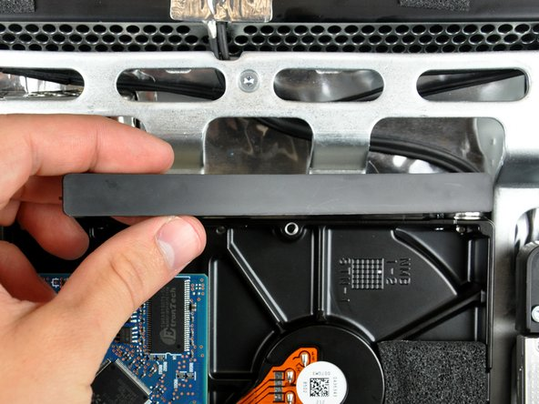 After the left edge has been freed, rotate the bracket toward the right edge of the hard drive.