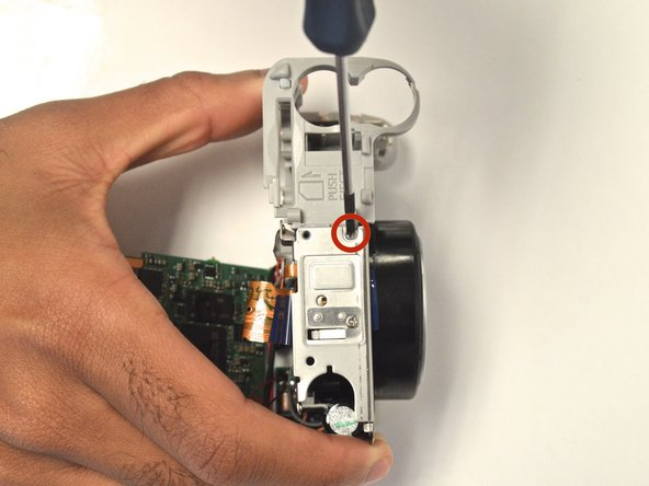 Turn the camera over so the bottom is exposed to remove the 30 mm Phillips head screw to disassemble the battery housing unit from the camera.