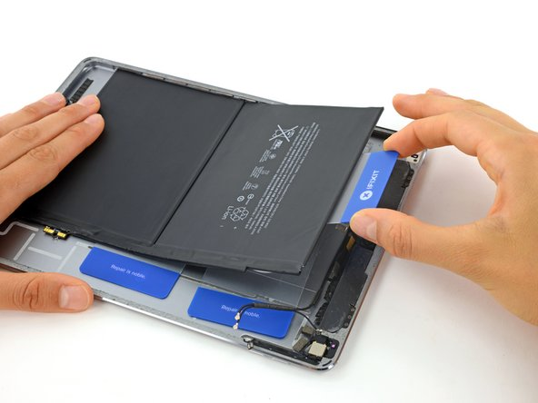 Image 3/3: Lift up on the card to pry the second battery cell up from the rear case.