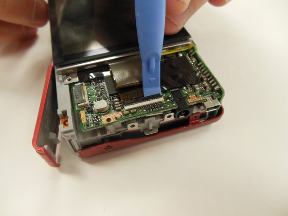 Using a plastic opening tool, gently lift ribbon clamp as indicated to remove the screen ribbon from the motherboard.