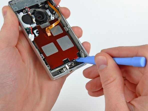 Use a plastic opening tool to pry the battery up off the outer case.
