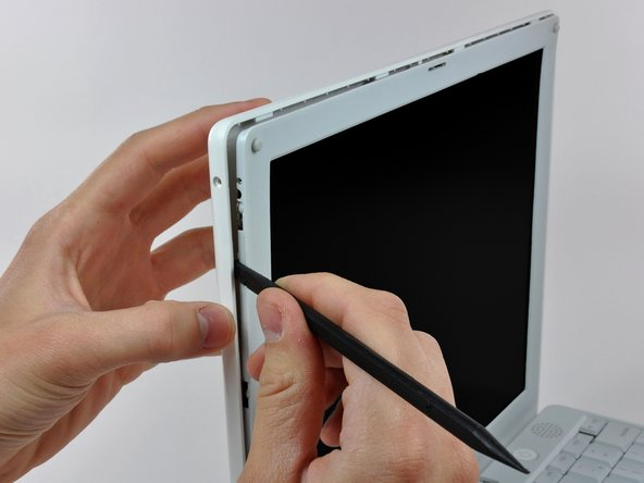 Working down from the upper left corner, use the flat end of a spudger to pry the rear bezel away from the left edge of the display.