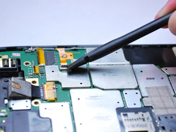 Release the yellow flex cable on the right side of the phone using the spudger by lifting up on the retaining clip.