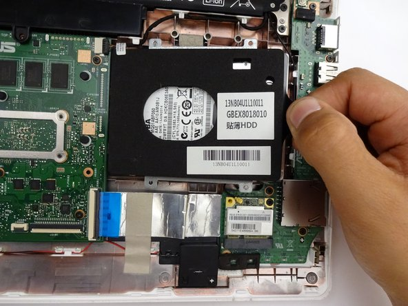Remove by sliding hard driving right and away from the computer using the tag on the right side.