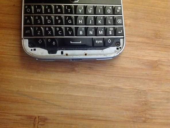 Like many other blackberry models, lift out the small plastic edge at the bottom of the keyboard