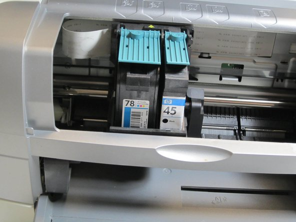 Notice the ink cartridges located in the center of the inside of the printer.  Note that the larger cartridge on the left holds the colored ink, and the thinner cartridge on the right holds the black ink.