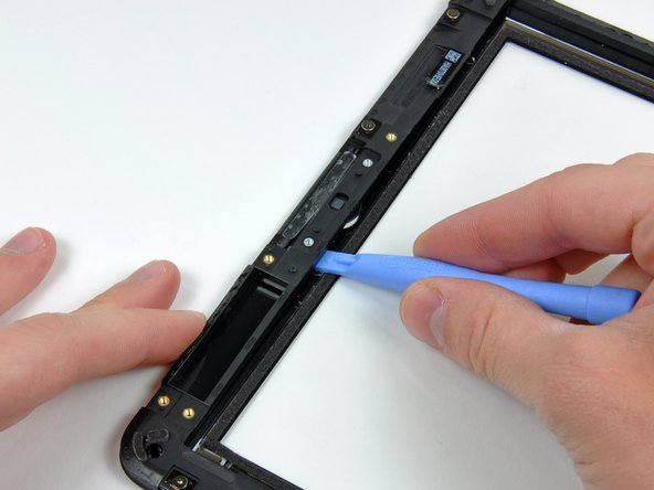 Image 1/2: Run your tool under the plastic display frame to separate it from the front glass near the home button area.