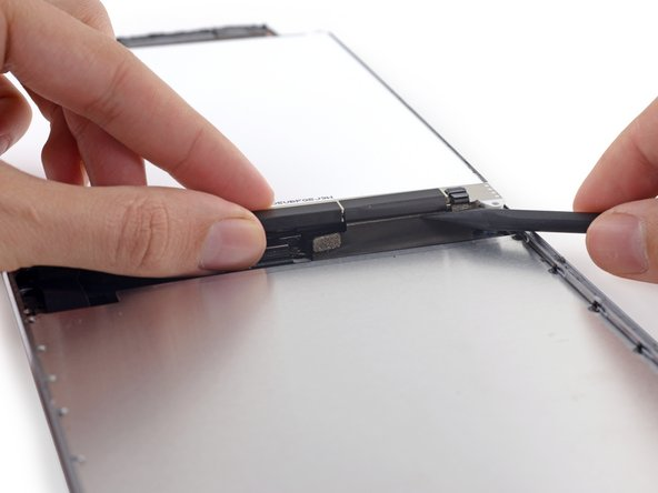 Image 1/3: Push gently between each of the two adhesive tabs; be careful not to damage any of the nearby cables.