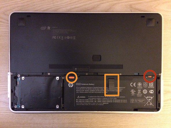 Image 1/2: Simultaneously slide the top left battery latch, pull on the battery tab, and remove the battery.