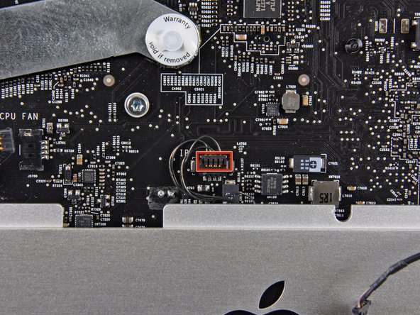 Image 2/2: Disconnect the IR sensor by pulling its connector toward the top edge of the iMac.