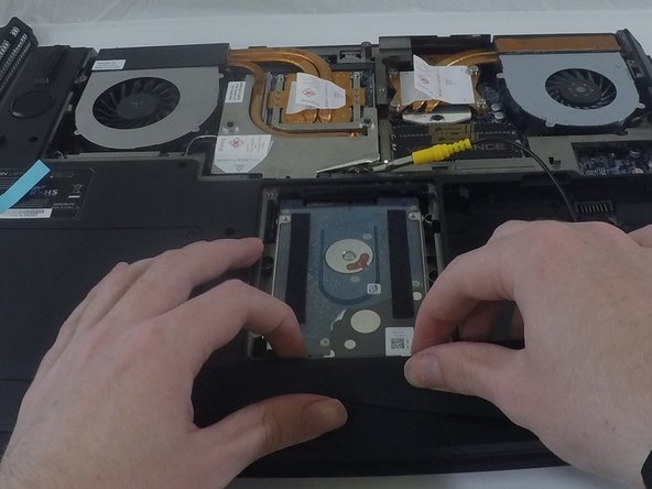 Image 1/2: Pull on the close end of the hard drive with the tips of your fingers to slide it towards you and out of its port.