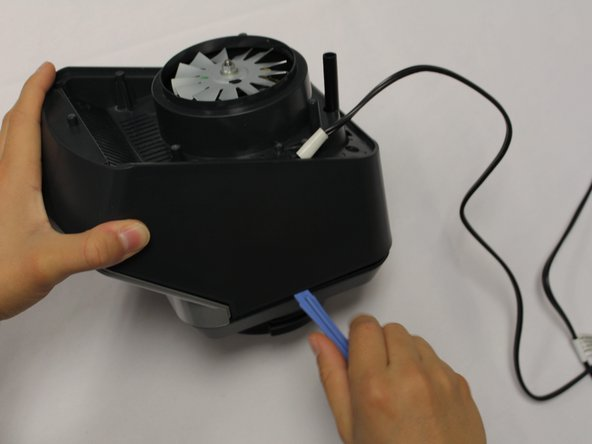 Using the iFixit plastic opening tool, pry the motor cover off the general housing. Once it is loose, lift it up to remove it off the base.