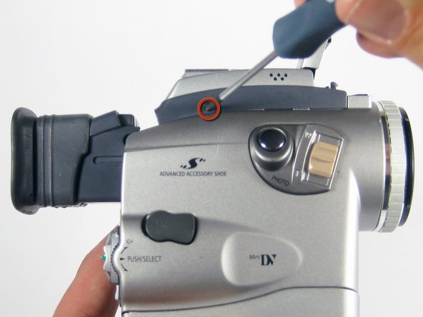 Image 1/1: Holding the camera as shown,remove the 4mm #00 Phillips screw.