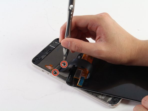 Use the T5 screwdriver to undo the two black, 4mm screws which hold the screen connector shield in place.