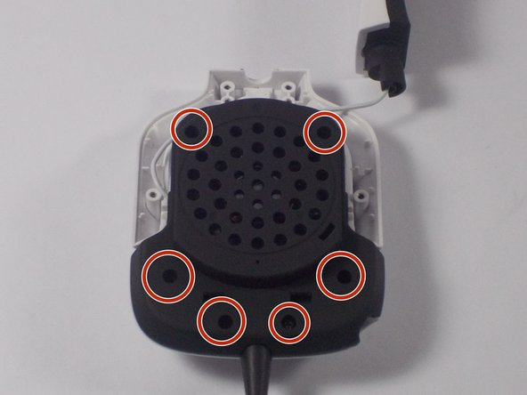 Unscrew the screws in the locations shown to remove the speaker cover.