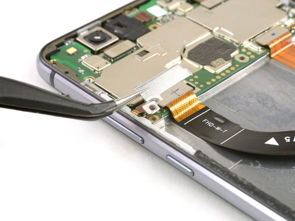Remove the metal shield which covers the display flex cable with tweezers.