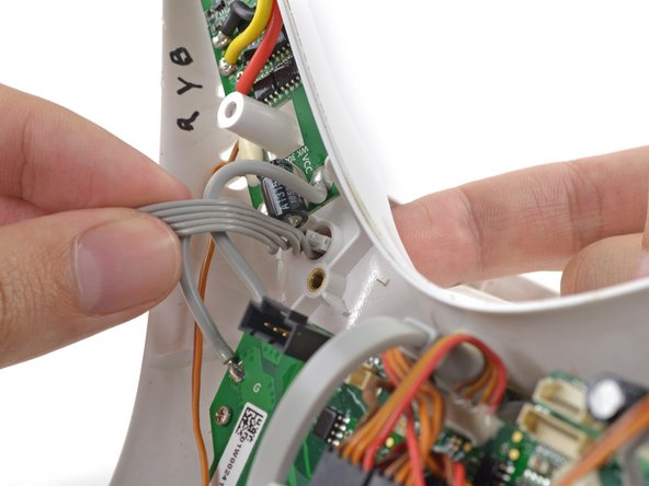 Gently push the twisted magnetometer cable and molex connector through the hole in the case bottom shell.