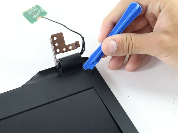 Using the blue plastic opening tool, pry up the squares that cover two screws on the front of the screen.