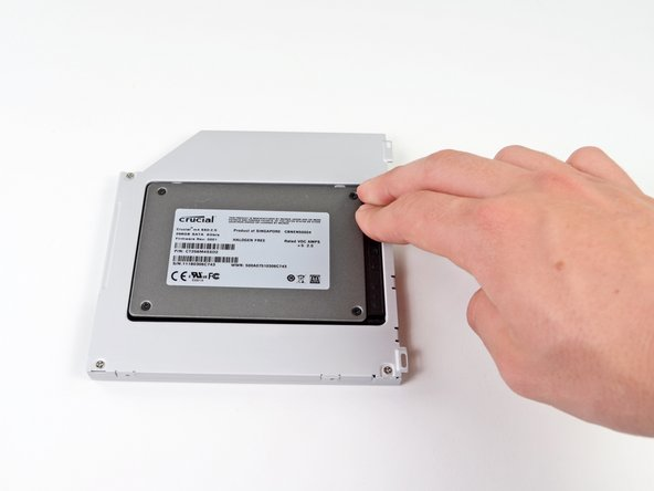 Once the hard drive is snug, reinsert the plastic spacer while holding the hard drive against the bottom of the enclosure.