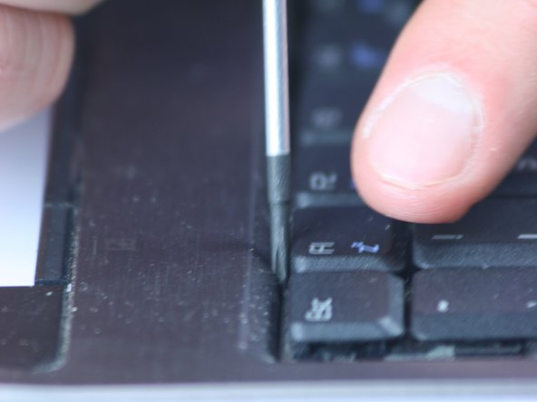 Starting on one side, use a finger or small tool to press the tab into the chassis of the computer. The edge of the keyboard will elevate. 72, 73