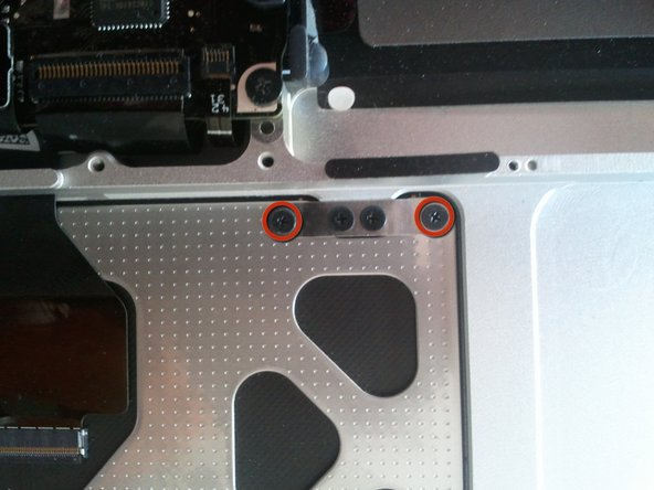 Remove the four 1.2mm #00 Phillips head screws from rear of the trackpad.