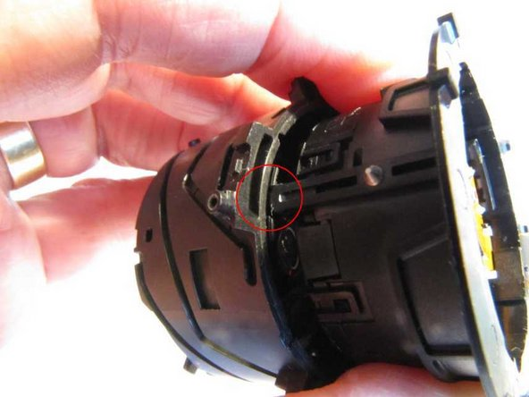 On reassembly, note a hole in the aperture and image stabilisation unit and a depression in the second lens carrier, located in the zoom control barrel. These need to line up. Three fingers on the aperture and stabilisation unit slide into slotted fingers on the second lens carrier.