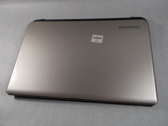 Close the laptop lid and flip it over so that Toshiba logo is facing down.