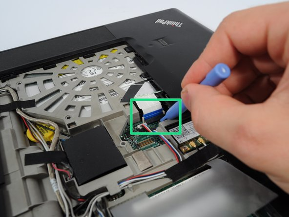 First, the ribbon cable that connects the trackpad to the motherboard needs to be removed.