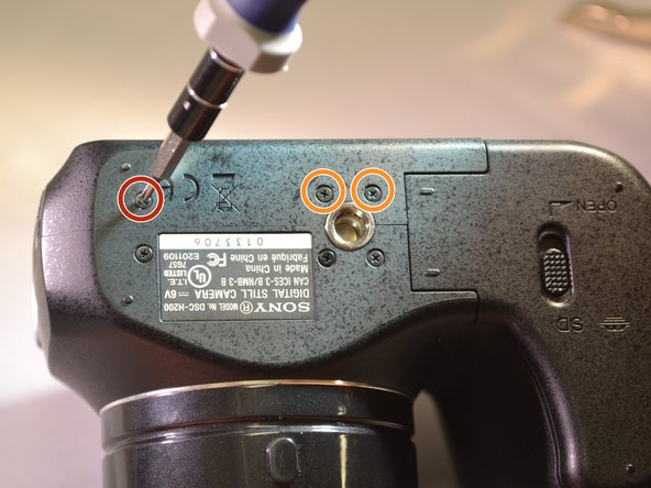Image 3/3: Using a screwdriver, remove the two 3mm screws located on the back panel.