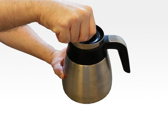 Twist the brew-through carafe lid counterclockwise to remove it.