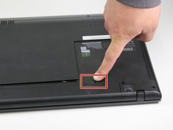 Image 1/2: With the battery facing you, slide the battery switch on the right side of the laptop towards the right.