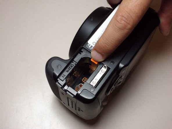 Pull the orange tab to the right to release the primary battery.