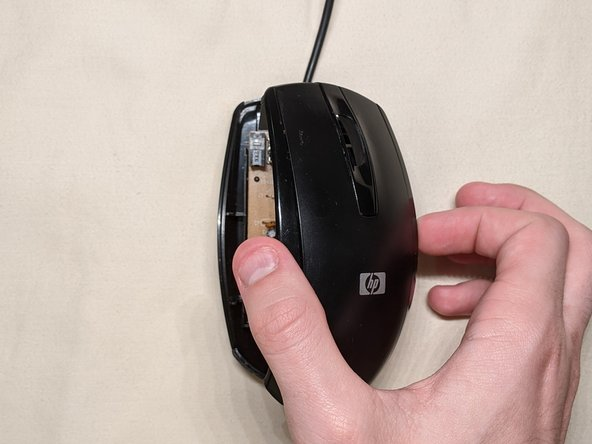 Gently flip the mouse back over and remove the upper half of the mouse casing.