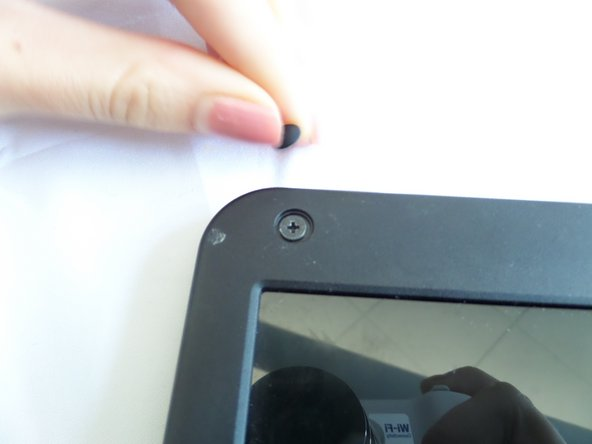 Remove rubber bumpers from each four corners to expose the hidden screws that hold the screen bezel in place.