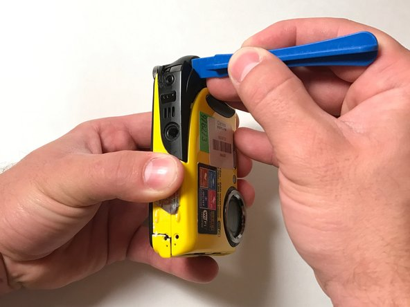 Continue using the opening tool on the bottom of the camera to gently pry the case apart.