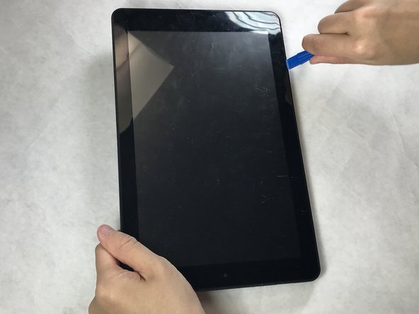 Insert plastic opening tool and slide it around the edges until the cover starts to pop off. It may be necessary to go over each side multiple times in order to pop the cover off.