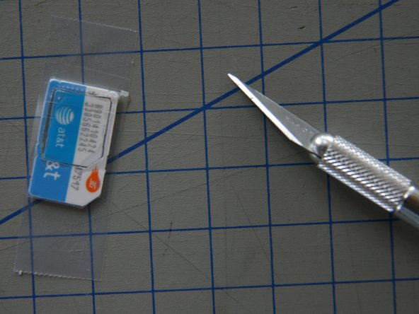 Image 2/3: If you cut the hole slightly too big, put a piece of tape over the back of the SIM-Card (the side without the gold contacts) to hold the Micro-SIM in place.   Trim away any excess tape with the knife.