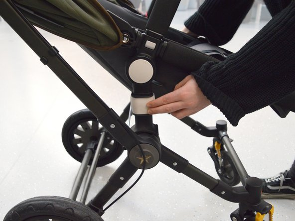 Push both the white square buttons under the seat at the same time, to remove the seat from the frame.