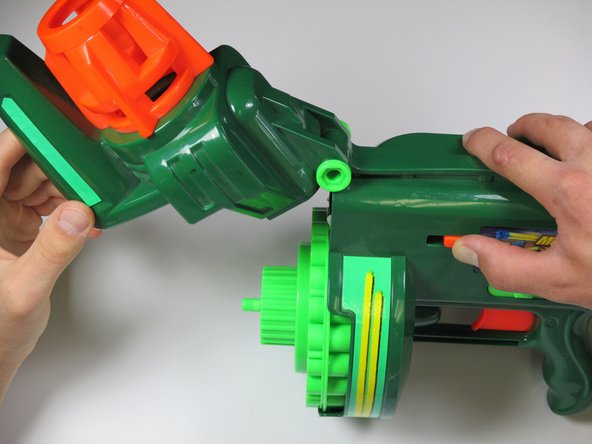 Pull the orange slider towards the back of the gun while lifting up on the nose the gun.