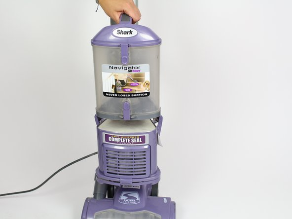 Remove the dust canister from the vacuum by lifting it up.