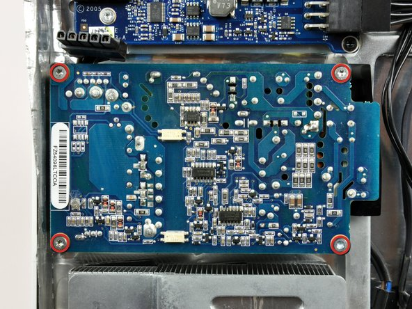 Remove the four T10 Torx screws securing the power supply to the rear case.