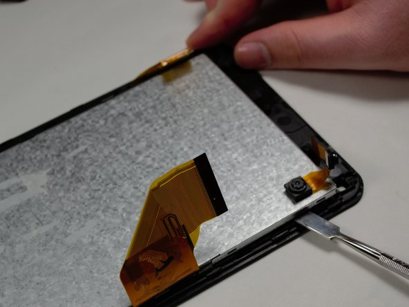 With the motherboard and battery detached, use the Metal Spudger tool to gently remove the display from the front panel.