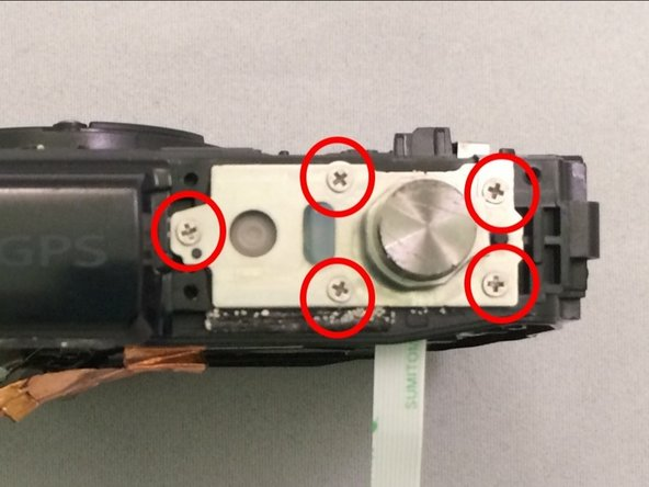 Remove the 5 Phillips #00 screws surrounding the shutter button.