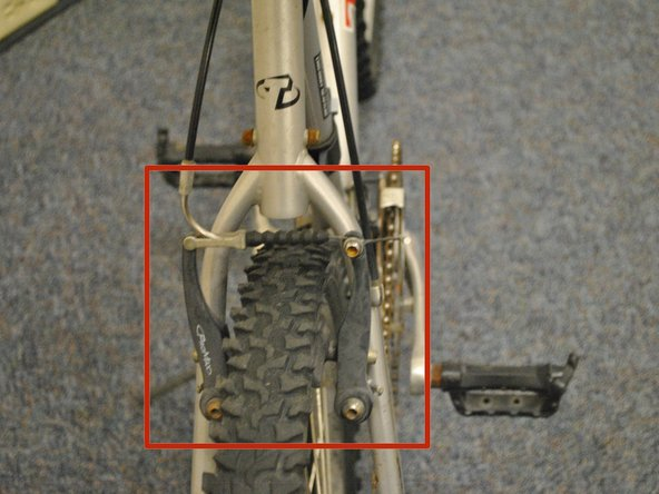 Start removing the rear tire by disengaging the rear brake.