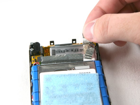Remove the silver tape from the bottom center and the top right. This allows access to the hard drive and the battery.
