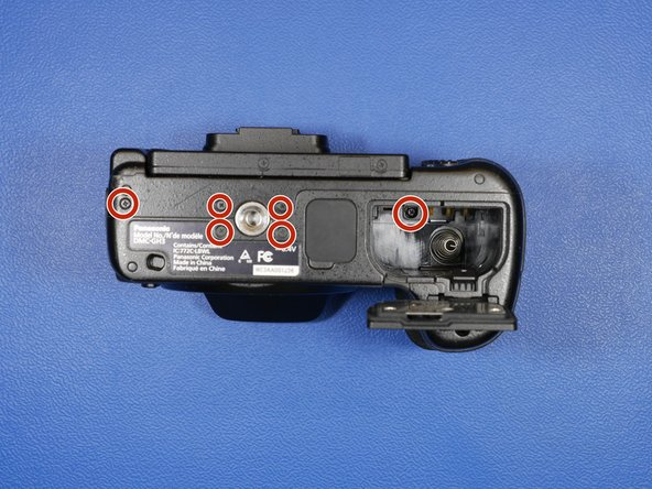 There are 6 screws on the bottom of the camera. One is hidden in the battery compartment.