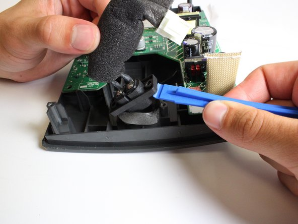 With an iFixit Plastic Opening Tool, pry the speaker port upwards and away from the socket.