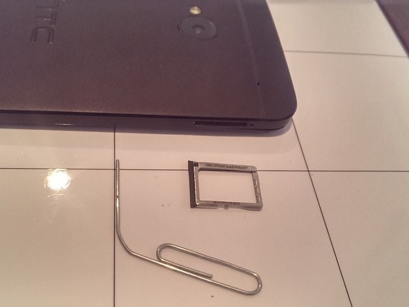 Remove the SIM card and tray by ejecting it with a paper clip or SIM Ejector Tool