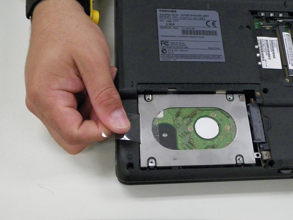 Hold plastic tab and gently pull tab slightly up and to the left to remove hard drive case from device.