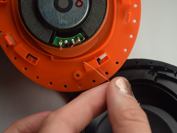 Image 1/2: Using the soldering iron, solder the wires to the new speaker.